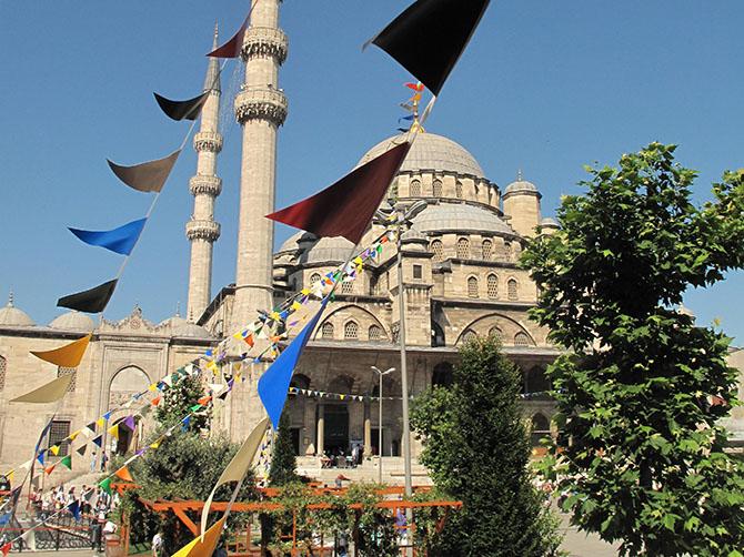 Une mosquée, des drapeaux, le ciel bleu.
